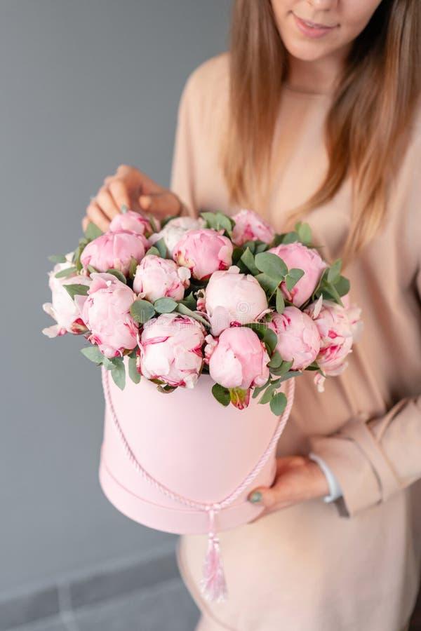 在桃红色圆的箱子的桃红色牡丹 美丽的牡丹花在编目或网络商店的妇女手上 花卉商店概念 免版税图库摄影