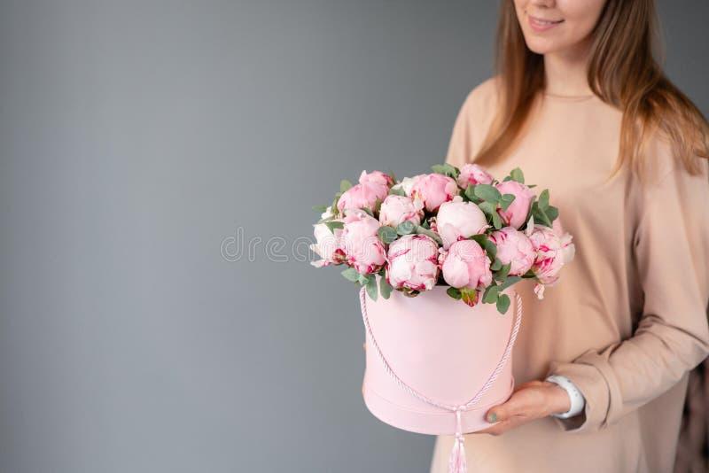 在桃红色圆的箱子的桃红色牡丹 美丽的牡丹花在编目或网络商店的妇女手上 花卉商店概念 库存图片