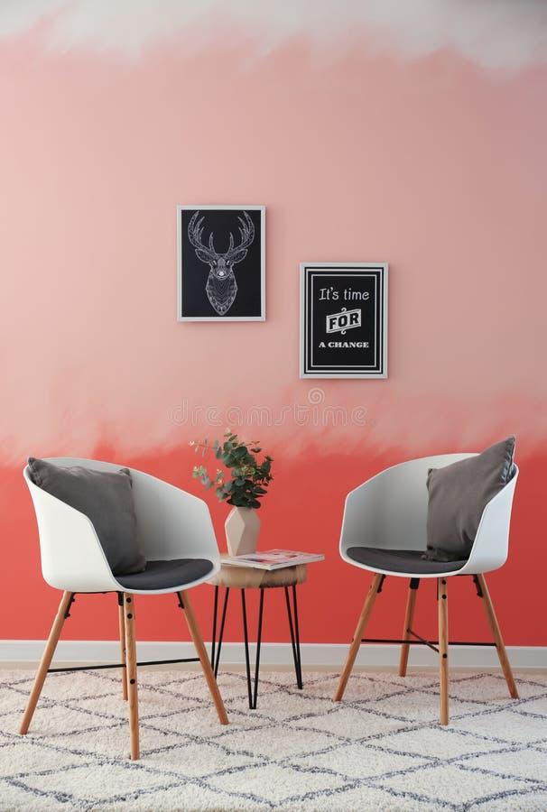 在桃红色墙壁附近的舒适的扶手椅子 免版税库存图片