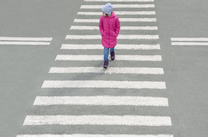 在桃红色外套、蓝色牛仔裤和帽子打扮的少女穿过路在行人交叉路在寒冷 从顶视图 库存图片