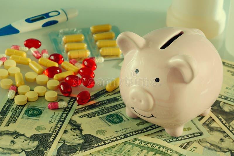 在桃红色存钱罐旁边驱散了片剂、胶囊和忧伤 概念,亲爱的医学 库存照片