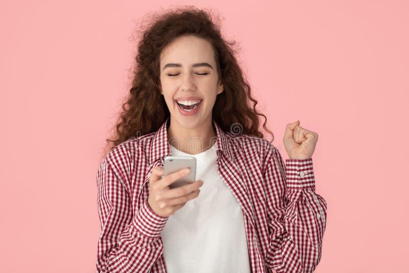 在桃红色接受了消息难以相信机会摆在隔绝的激动的女孩 免版税库存图片