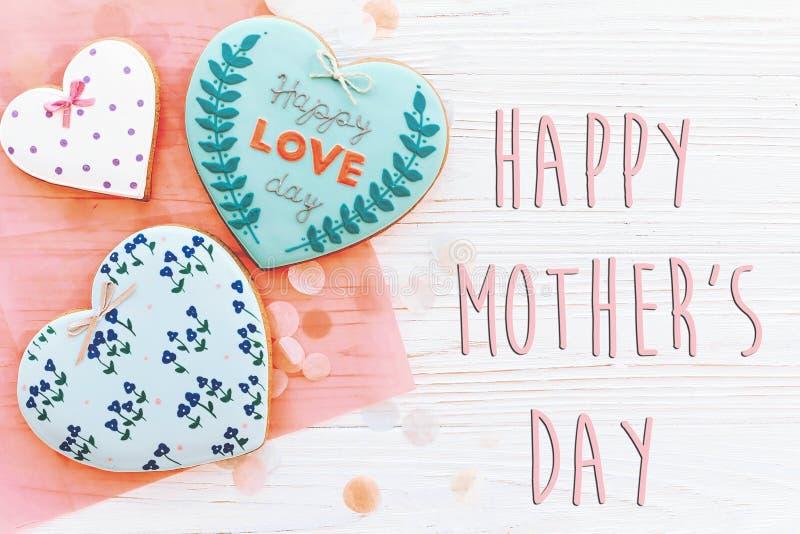 在桃红色曲奇饼心脏的愉快的母亲` s天文本在白色土气wo 图库摄影