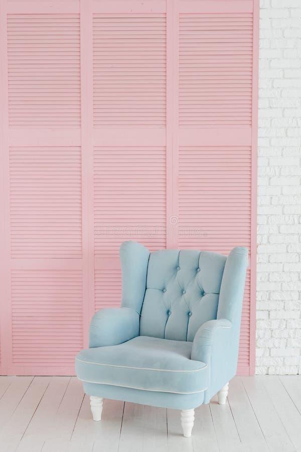 在桃红色木背景的软的蓝色空的扶手椅子 库存照片