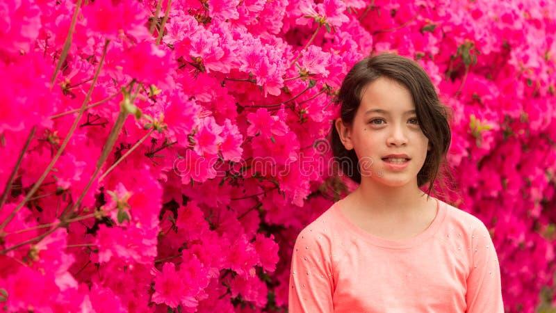 在桃红色杜娟花花前面的年轻亚洲青少年的身分在T恤杉在温泉天 免版税图库摄影