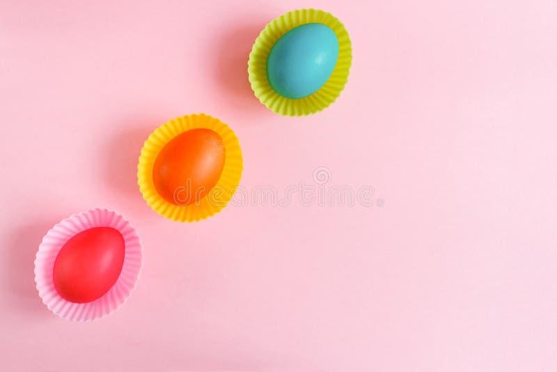 在桃红色杯形蛋糕模子的平的位置三复活节被绘的鸡蛋diadonally在与拷贝空间的桃红色背景说谎 免版税库存图片