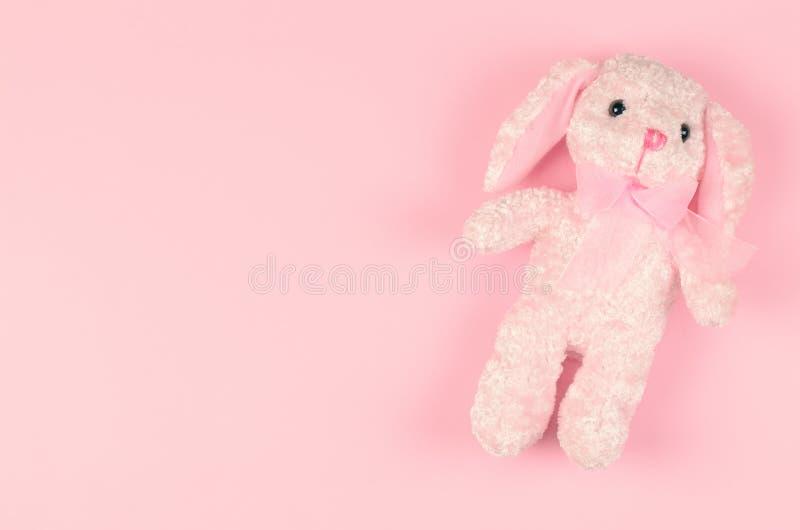 在桃红色柔和的背景的少女软的玩具 图库摄影
