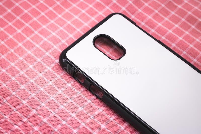 在桃红色桌布背景的黑流动盖子 电话盒和白色表面后面看法您的设计的 库存照片