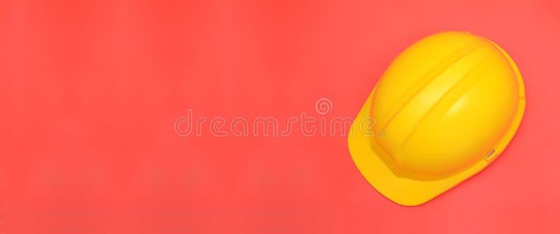 在桃红色横幅模板的黄色安全帽 库存图片