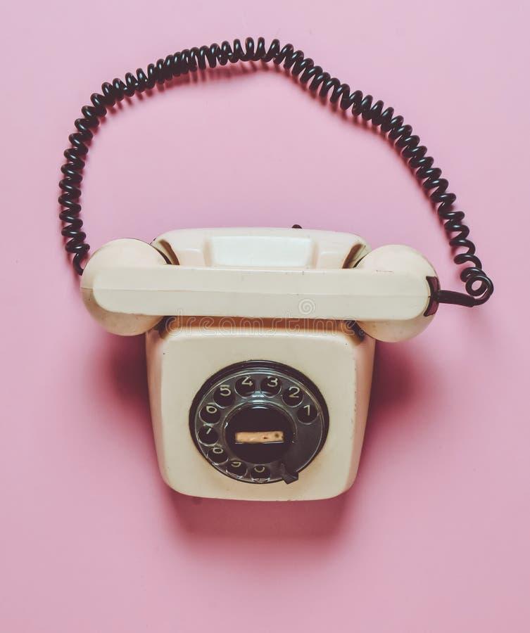 在桃红色淡色背景的转台式减速火箭的电话 热线 热线服务电话 顶视图 免版税库存照片