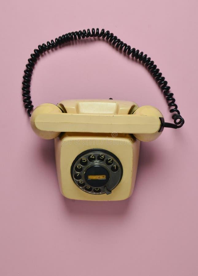 在桃红色淡色背景的转台式减速火箭的电话 热线 顶视图 免版税库存照片