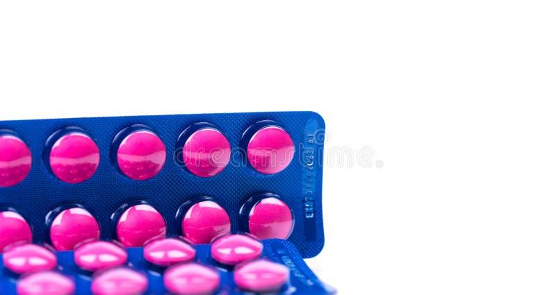 在桃红色片剂药片的异丁苯丙酸在与拷贝空间的白色背景隔绝的蓝色天线罩包装包装 安心痛苦的异丁苯丙酸 免版税库存照片