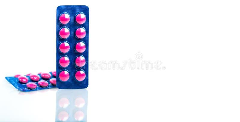 在桃红色片剂药片的异丁苯丙酸在白色背景的蓝色天线罩包装包装与拷贝空间 安心痛苦的异丁苯丙酸 图库摄影