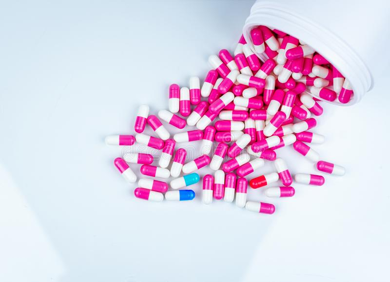 在桃红色白的胶囊药片沾染的青白的胶囊 胶囊药片传播了在塑料药物瓶外面 ?? 库存照片