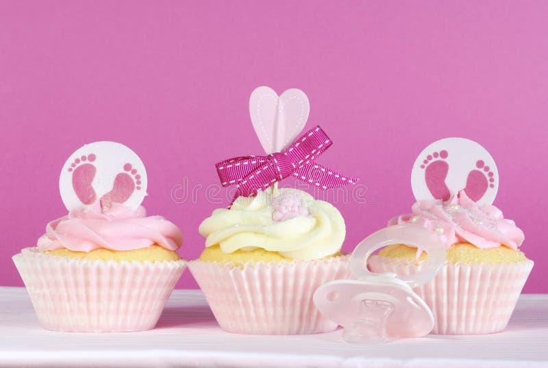 在桃红色的三块桃红色题材女婴杯形蛋糕 库存照片