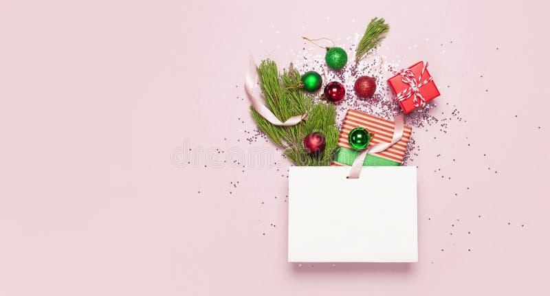 在桃红色的平的被放置的顶视图白色礼物袋子全息照相的闪烁五彩纸屑红色绿色圣诞节球杉木分支礼物盒 库存图片