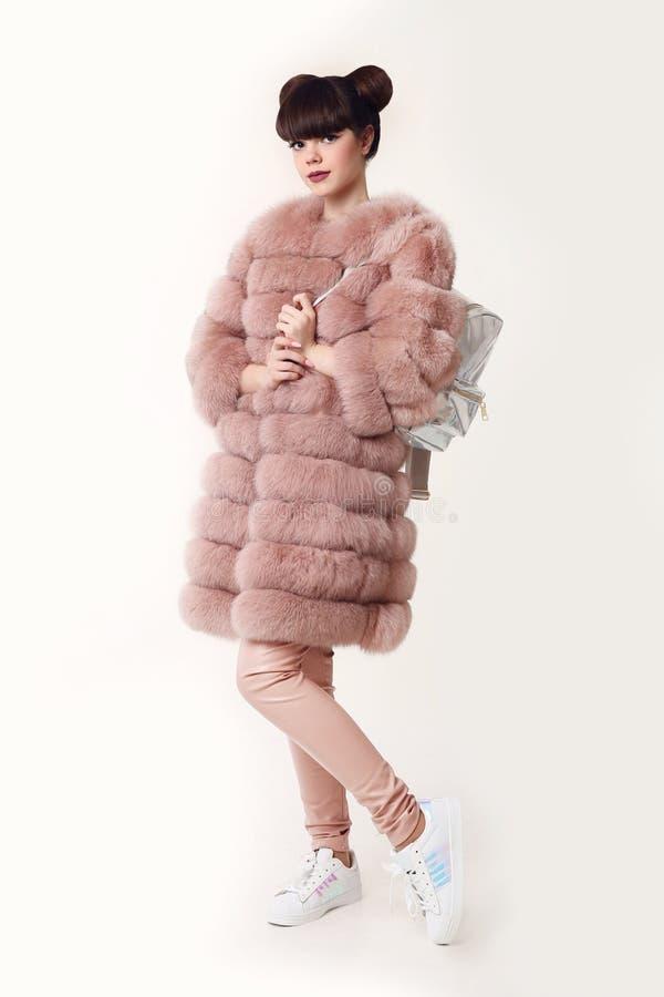 在桃红色皮大衣的时尚演播室青少年的神色样式给backpa做广告 免版税库存照片