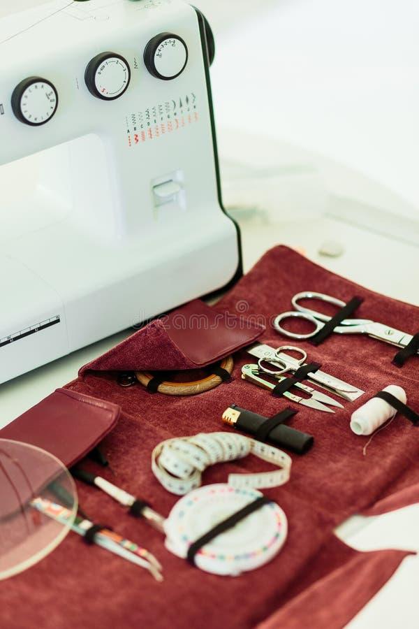 在桃红色盖子和机器的针线包辅助部件 免版税库存图片