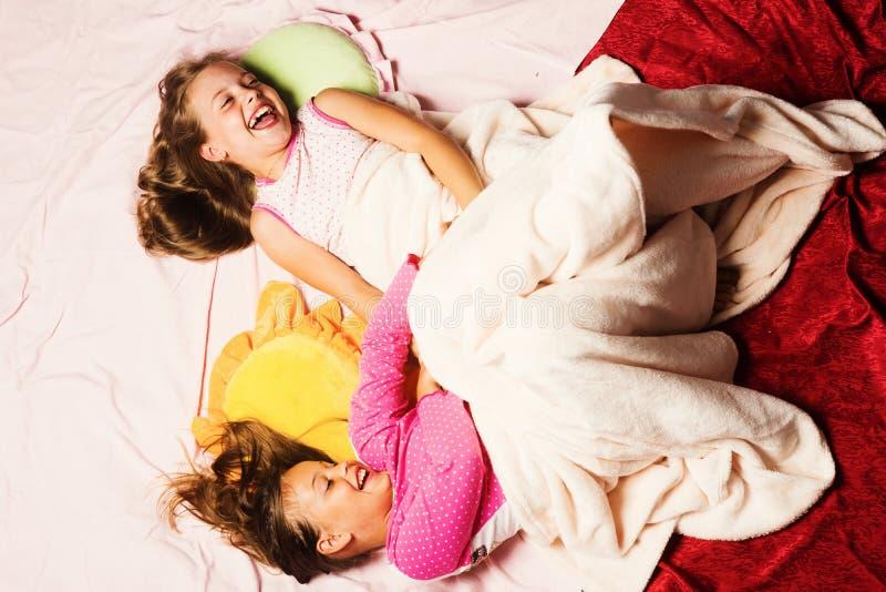 在桃红色睡衣的孩子无所事事  与枕头的女小学生戏剧 免版税库存照片