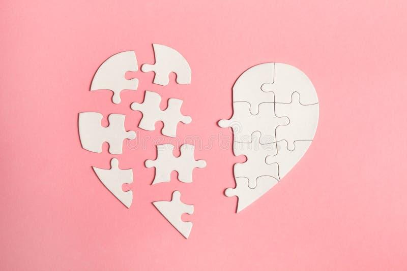 在桃红色背景、顶视图,平的位置、离婚、消沉和终止概念隔绝的拼图心脏,哭泣,医疗卡片 免版税库存图片