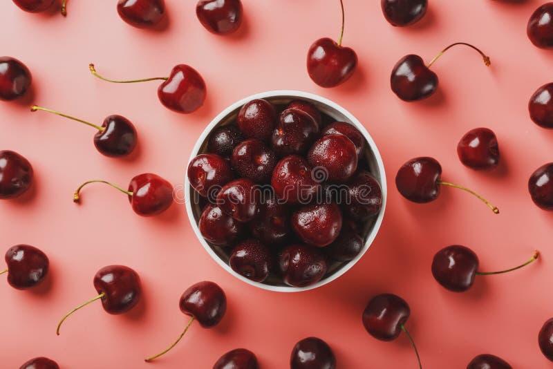 在桃红色背景在一个白色杯子,顶视图的樱桃莓果 库存图片
