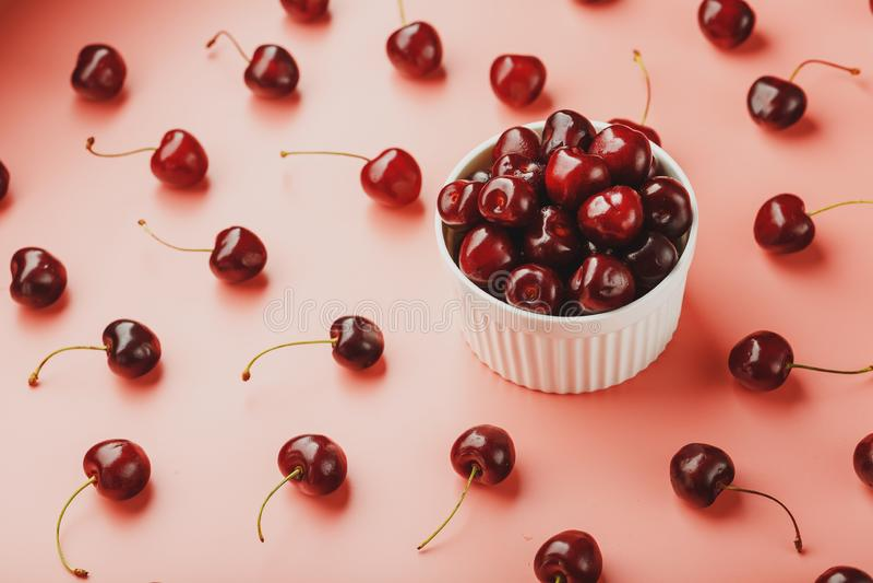 在桃红色背景在一个白色杯子,顶视图的樱桃莓果 库存照片