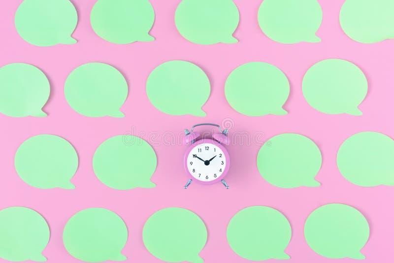 在桃红色背景是一个小桃红色闹钟 在它附近是被胶合的空的浅绿色的贴纸 在上面的明亮的照片 图库摄影