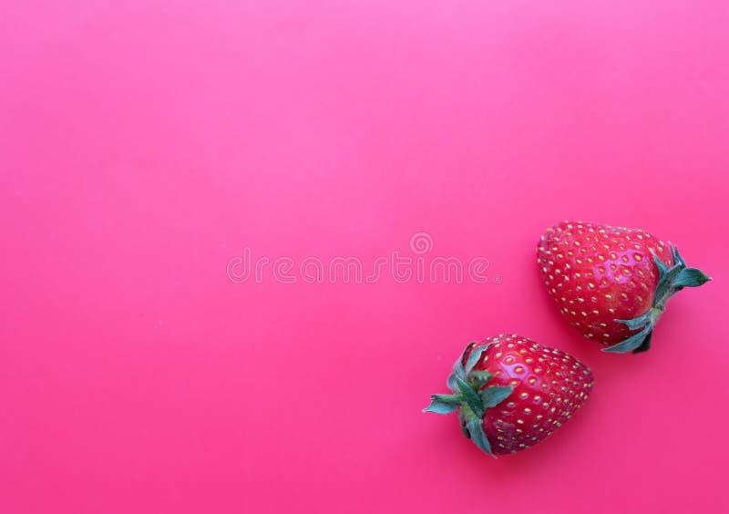 在桃红色背景的两个草莓 库存图片