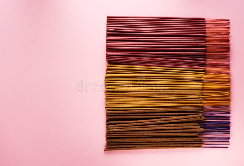 在桃红色背景的五颜六色的香火棍子 库存图片