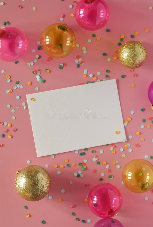 在桃红色背景的大模型卡片与他们的圣诞节装饰和五彩纸屑 邀请,卡片,纸 安置文本 图库摄影