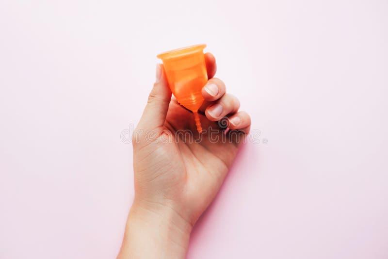 在桃红色背景的妇女的手藏品月经杯子 免版税库存照片