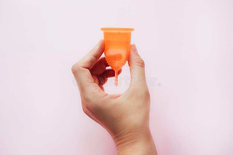 在桃红色背景的妇女的手藏品月经杯子 图库摄影