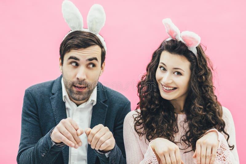 在桃红色背景的年轻家庭 复活节愉快的夫妇 节假日 一个微小的耳朵 从兔子耳朵的人们 推托做 免版税库存照片
