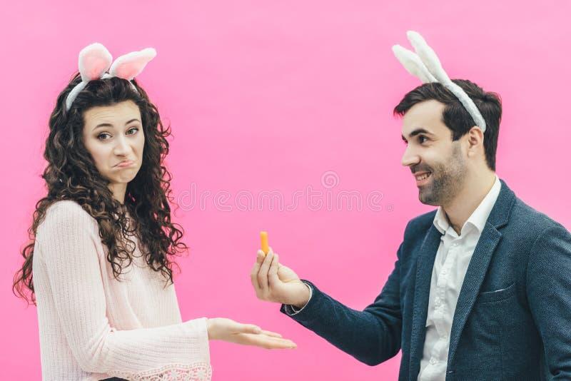 在桃红色背景的年轻愉快的夫妇 在头上是兔子耳朵 年轻人在他的手上的拿着一棵小红萝卜 免版税图库摄影