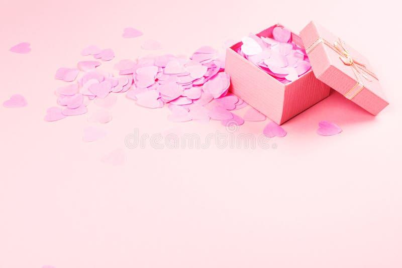 在桃红色背景的当前箱子与多彩多姿的五彩纸屑 库存图片