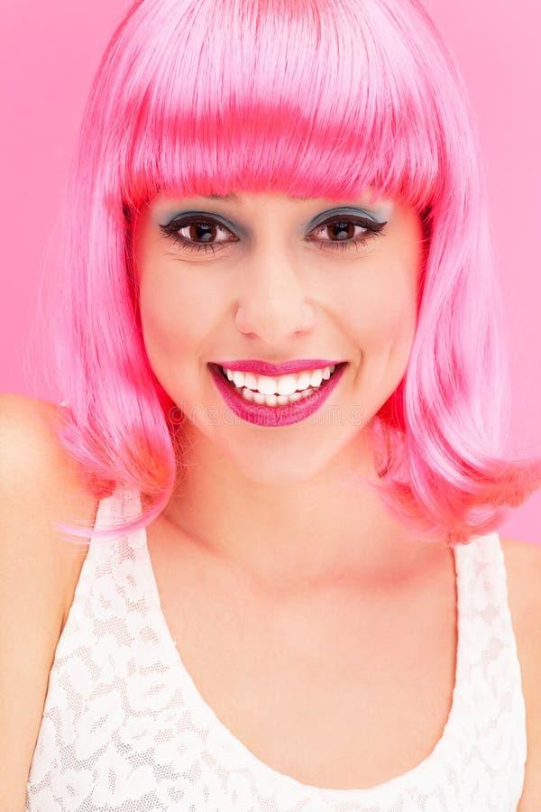 在桃红色背景的微笑的妇女