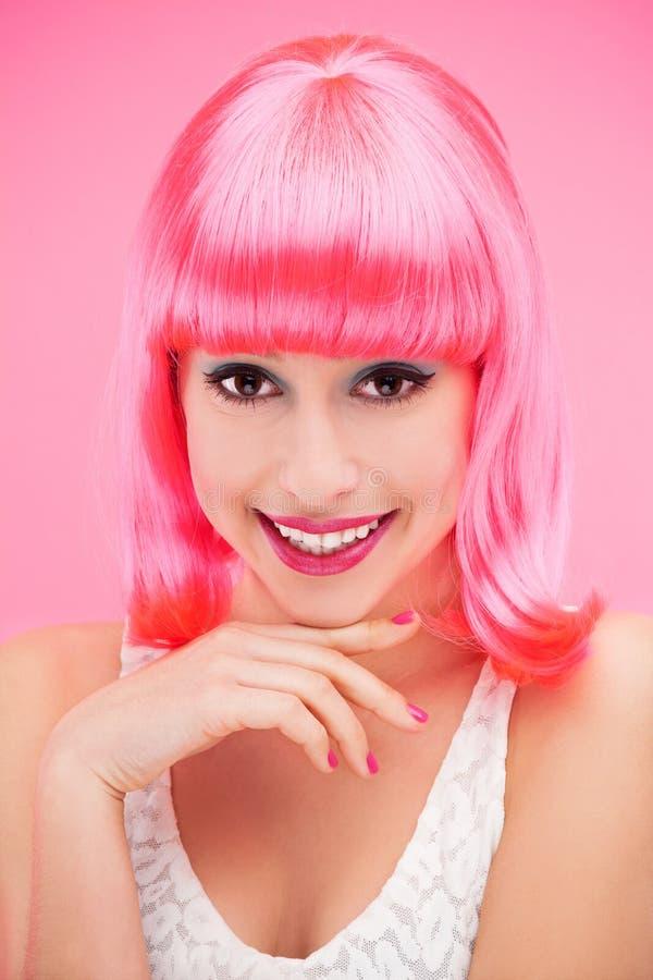 在桃红色背景的微笑的妇女 库存照片