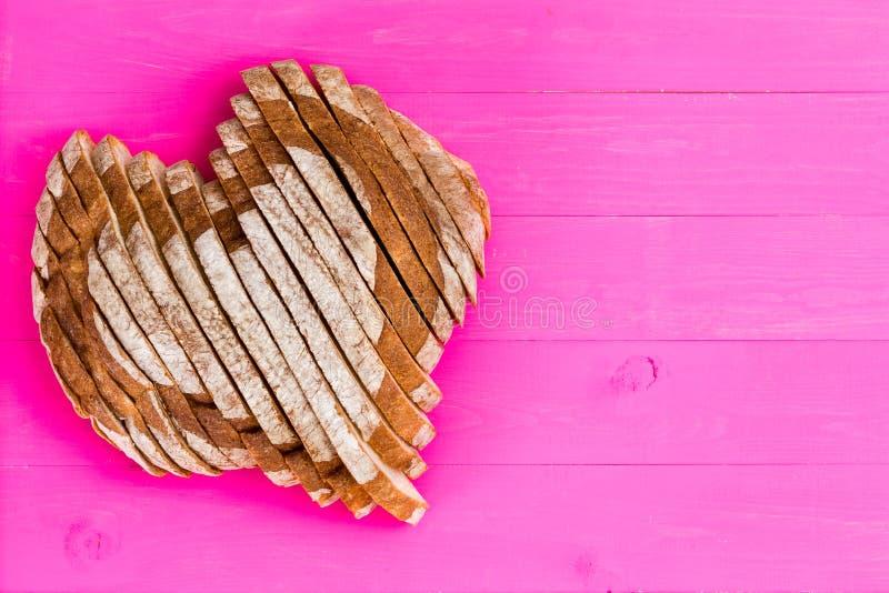 在桃红色背景的心形的切的面包 库存照片