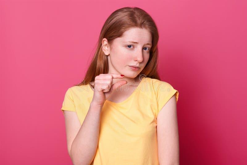 在桃红色背景的打手势用手的年轻可爱的女小学生接近的画象,显示小型标志, 免版税库存图片