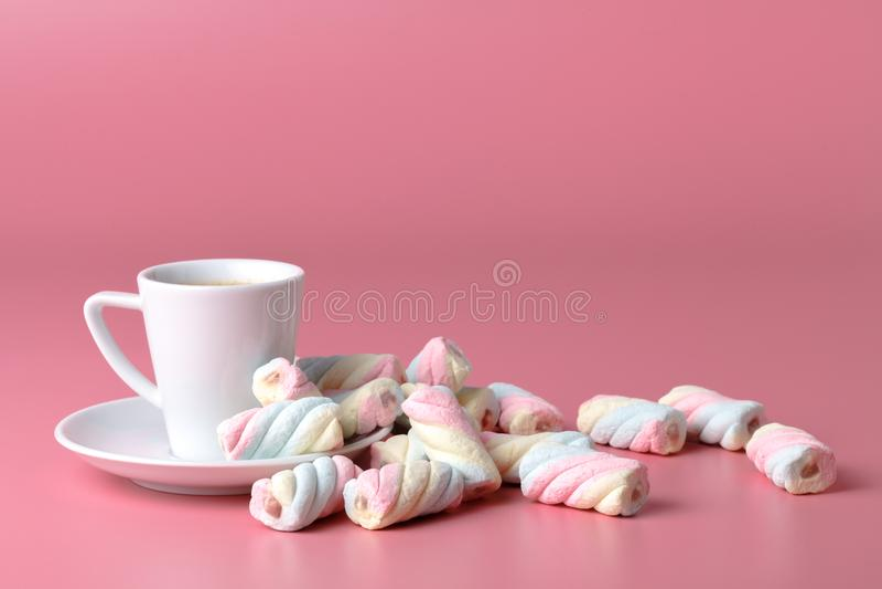 在桃红色背景的扭转的美国蛋白软糖与咖啡杯 免版税库存图片