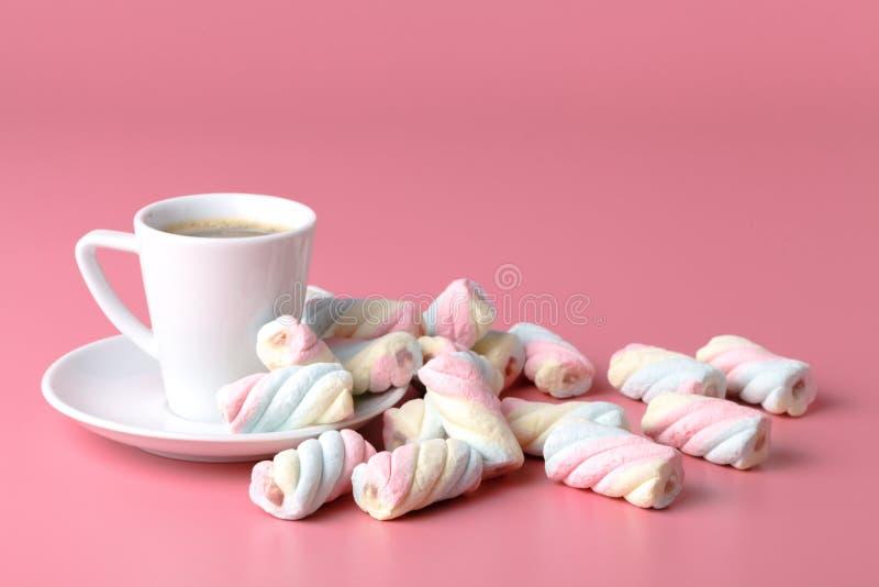 在桃红色背景的扭转的美国蛋白软糖与咖啡杯 库存照片