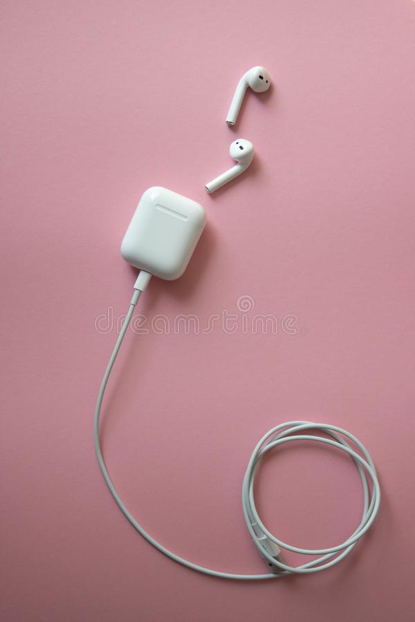 在桃红色背景的无线白色耳机 Airpods 有充电器的白色无线耳机被连接到被盘绕的电缆 免版税库存图片