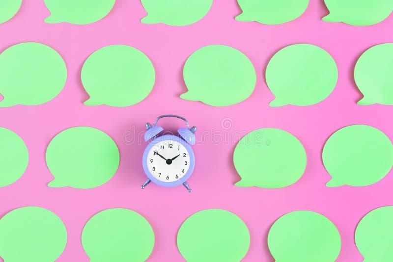 在桃红色背景的明亮,空的浅绿色的标签 在中心是一个小淡紫色闹钟 概念,美好 免版税库存照片