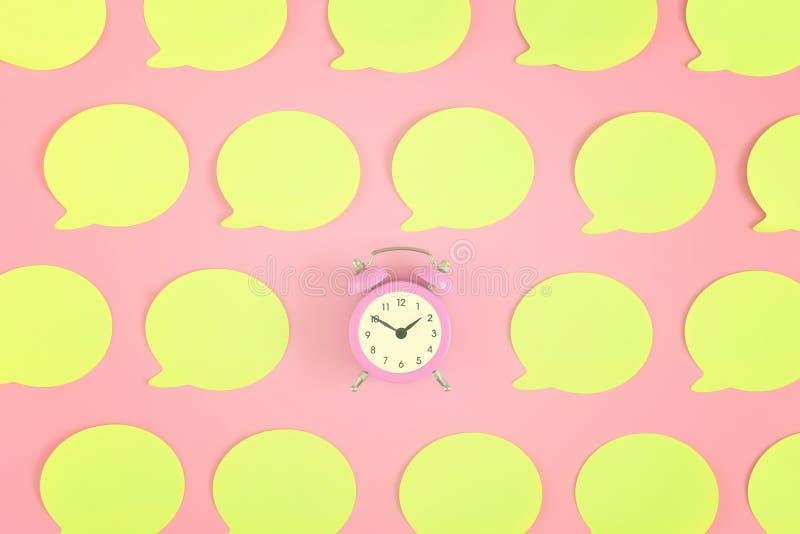 在桃红色背景的明亮,空的黄色贴纸 在中心是一个小桃红色闹钟 免版税库存图片