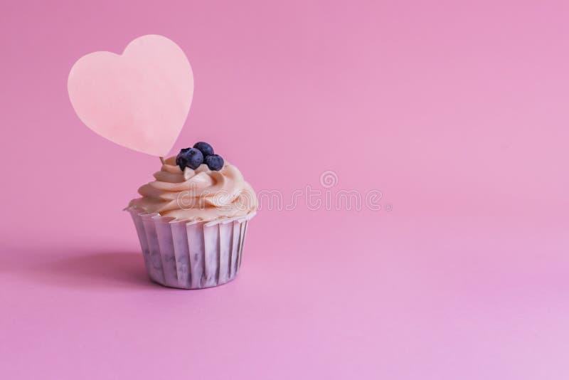 在桃红色背景的松饼蛋糕与题字的一个地方以心脏的形式 库存照片