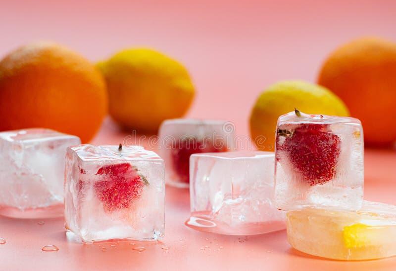 在桃红色背景的果子构成,关闭看法 草莓和以冰形式结冰的柠檬切片 桔子,黄色 免版税库存照片
