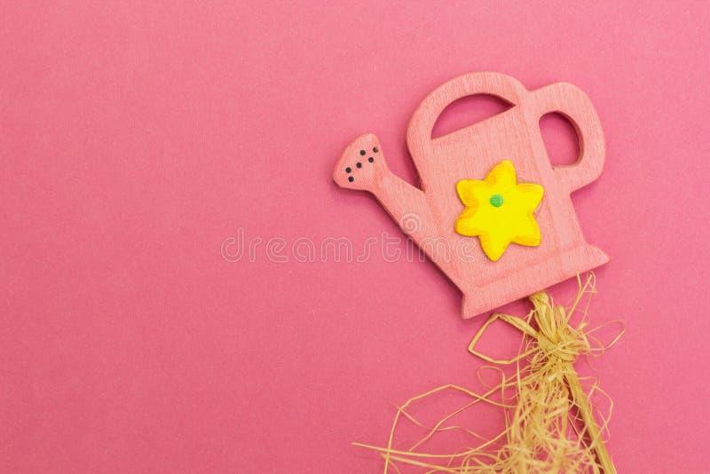 在桃红色背景的桃红色喷壶,儿童的比赛 图库摄影