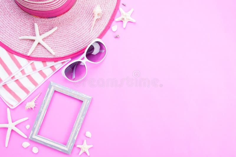 在桃红色背景的海滩辅助部件相框、太阳镜、海星、海滩帽子和海壳为夏天休假和假期 免版税库存照片