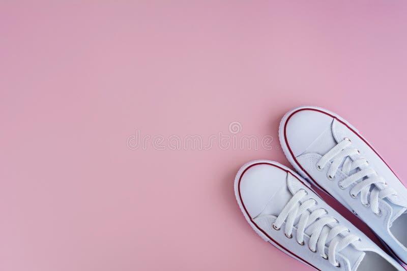在桃红色背景的白色sneackers 库存照片