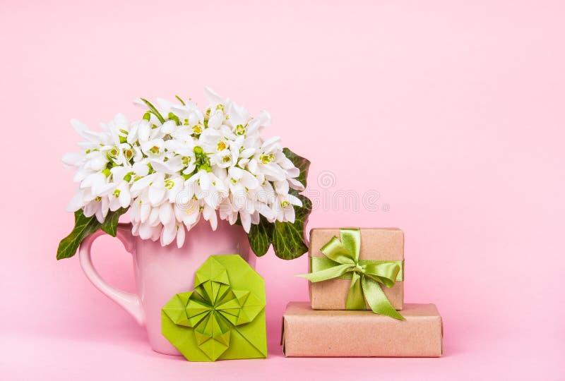 在桃红色背景的白花 花、origami心脏和礼物盒 免版税库存图片